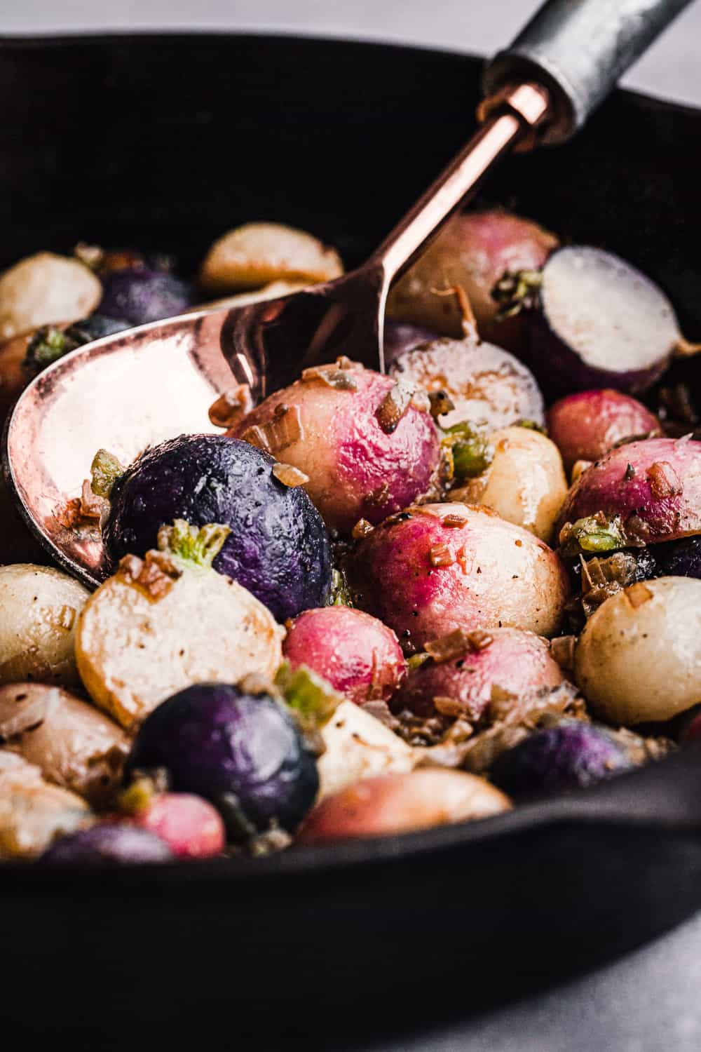 roasted round radishes, cut in half, in a cast iron skillet with a gold and silver serving spoon