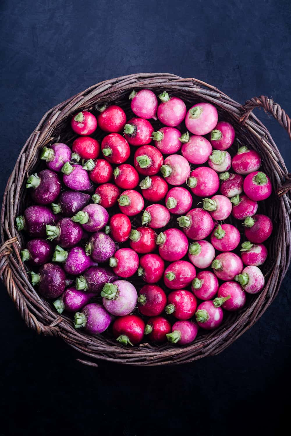 a basked of purple, red and pink round radishes, overhead shot on a black background
