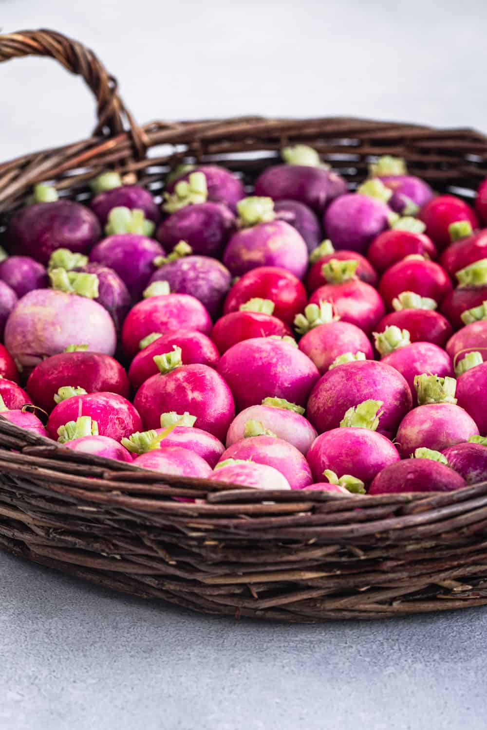 side angle shot of pink, red and purple round radishes in a basked on a light background
