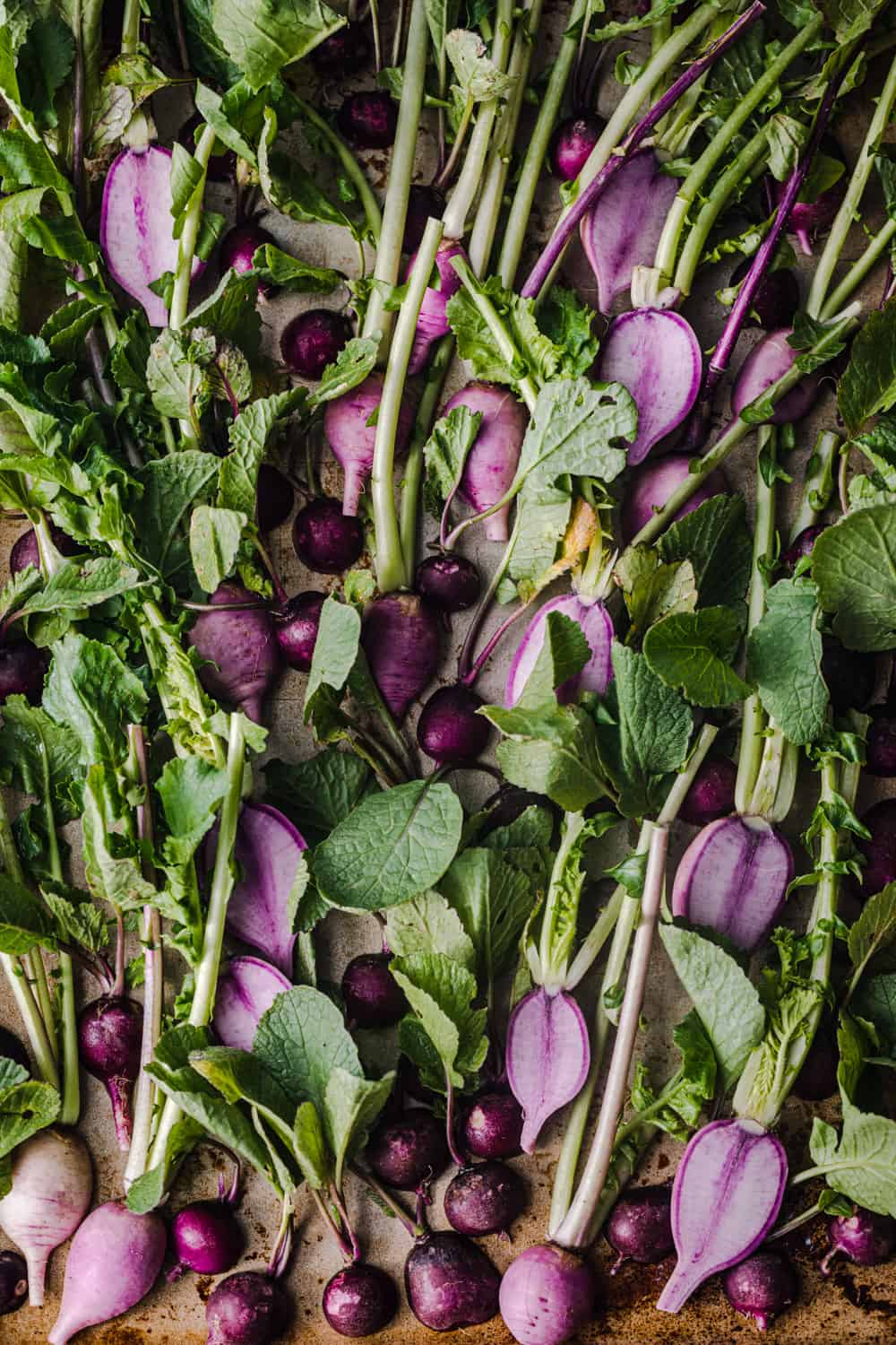 Ninja and purple round radishes cut in half with their leafy green tops still on, overhead shot on a baking sheet