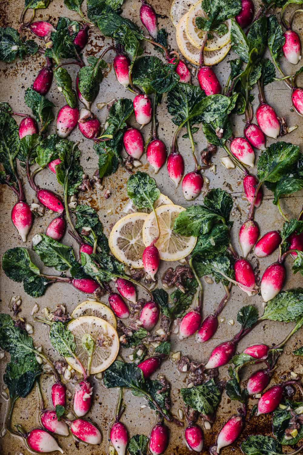 small French breakfast radishes cut in half and ready to be roasted; they are tossed with garlic, anchovies, lemon slices, olive oil, salt and pepper.