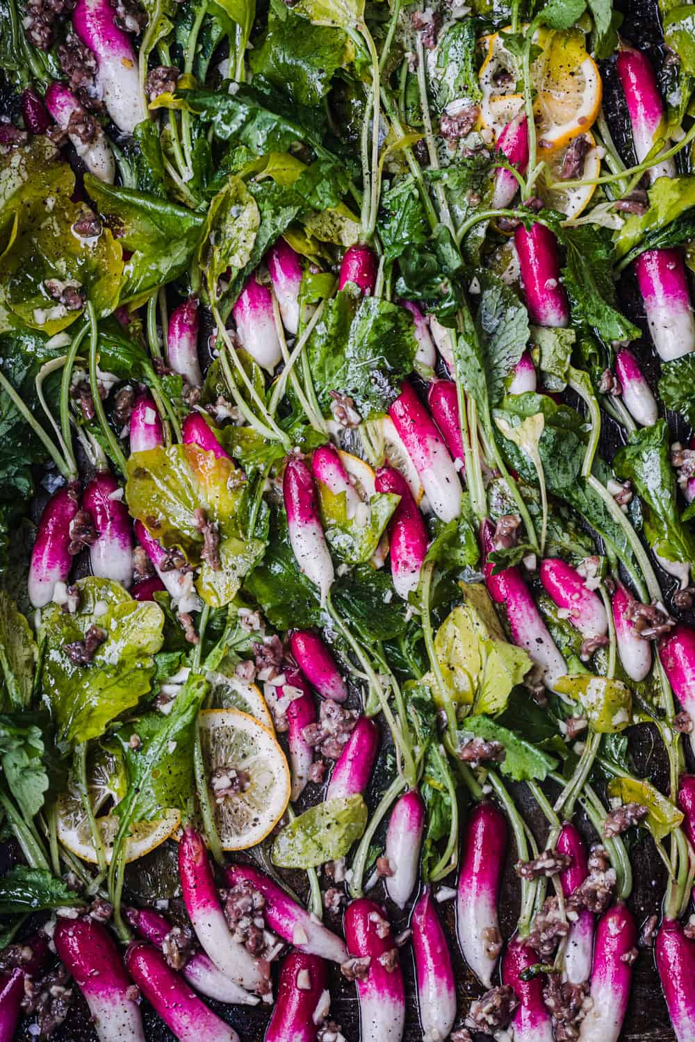 pre-oven shot of French breakfast radishes with their leafy green tops still on, tossed with garlic and anchovies