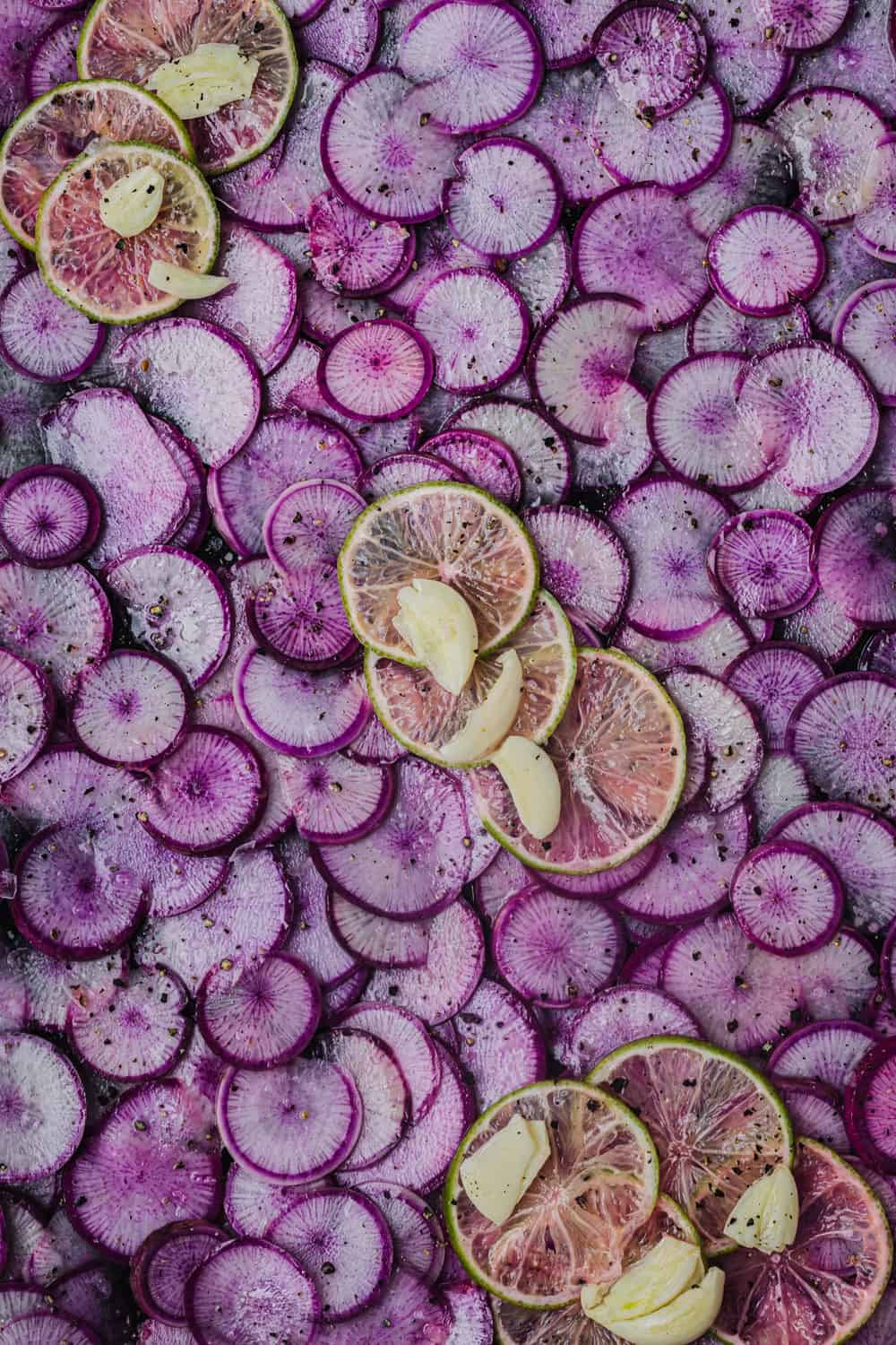 thinly sliced purple ninja radishes, with thinly sliced lime and garlic