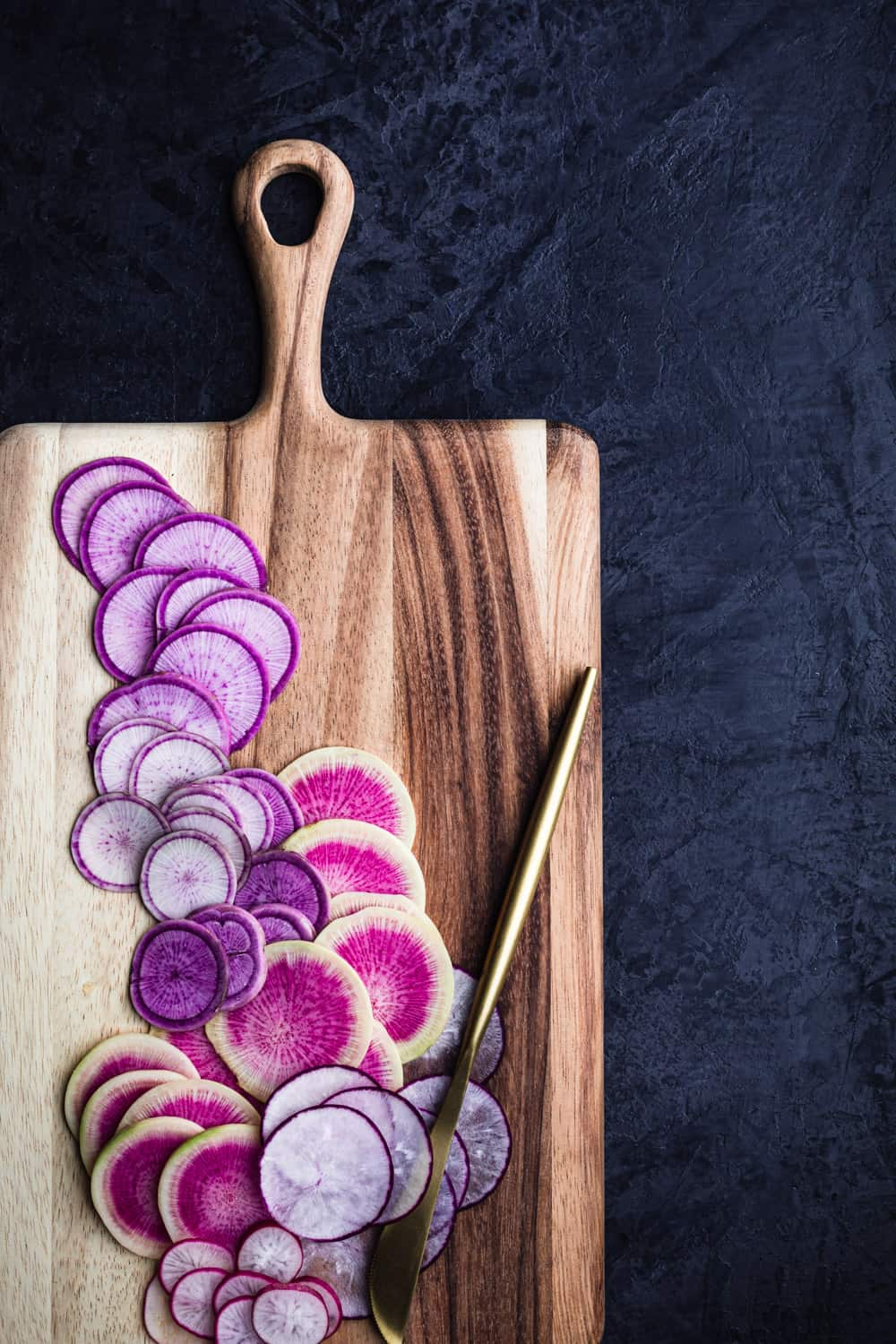 Ninja, watermelon, Cincinnati and round radishes, thinly sliced on a wood cutting board on a black background