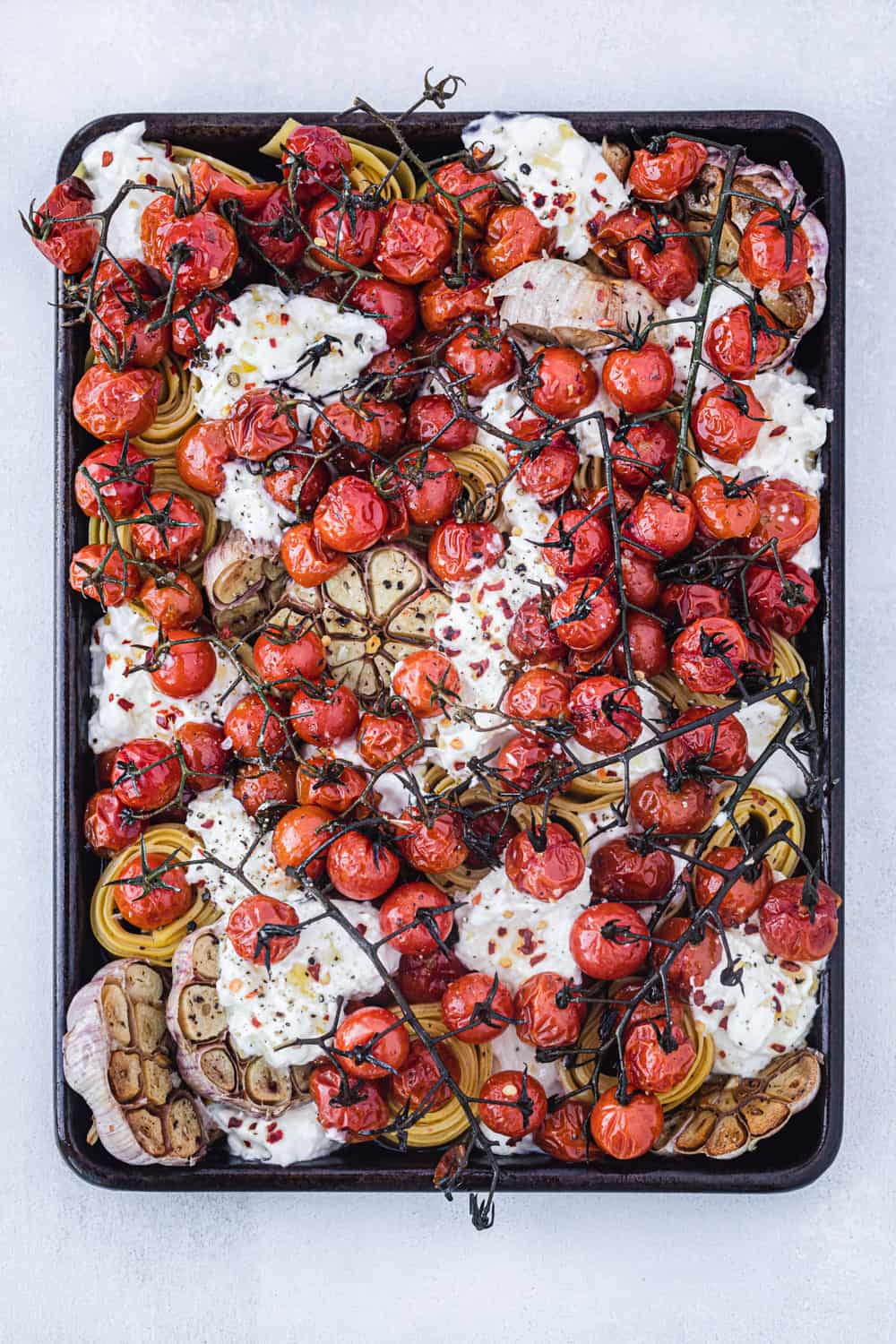 overhead shot of the pasta with cherry tomatoes, burrata, garlic chili flakes, salt and pepper arranged on a baking sheet on a white background.