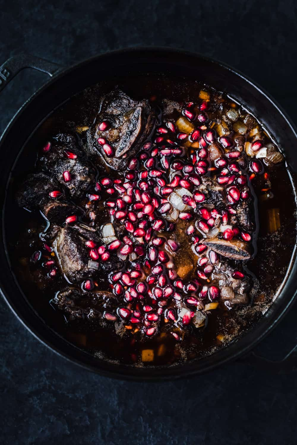 red wine braised short ribs, with pomegranate arils , overhead shot.