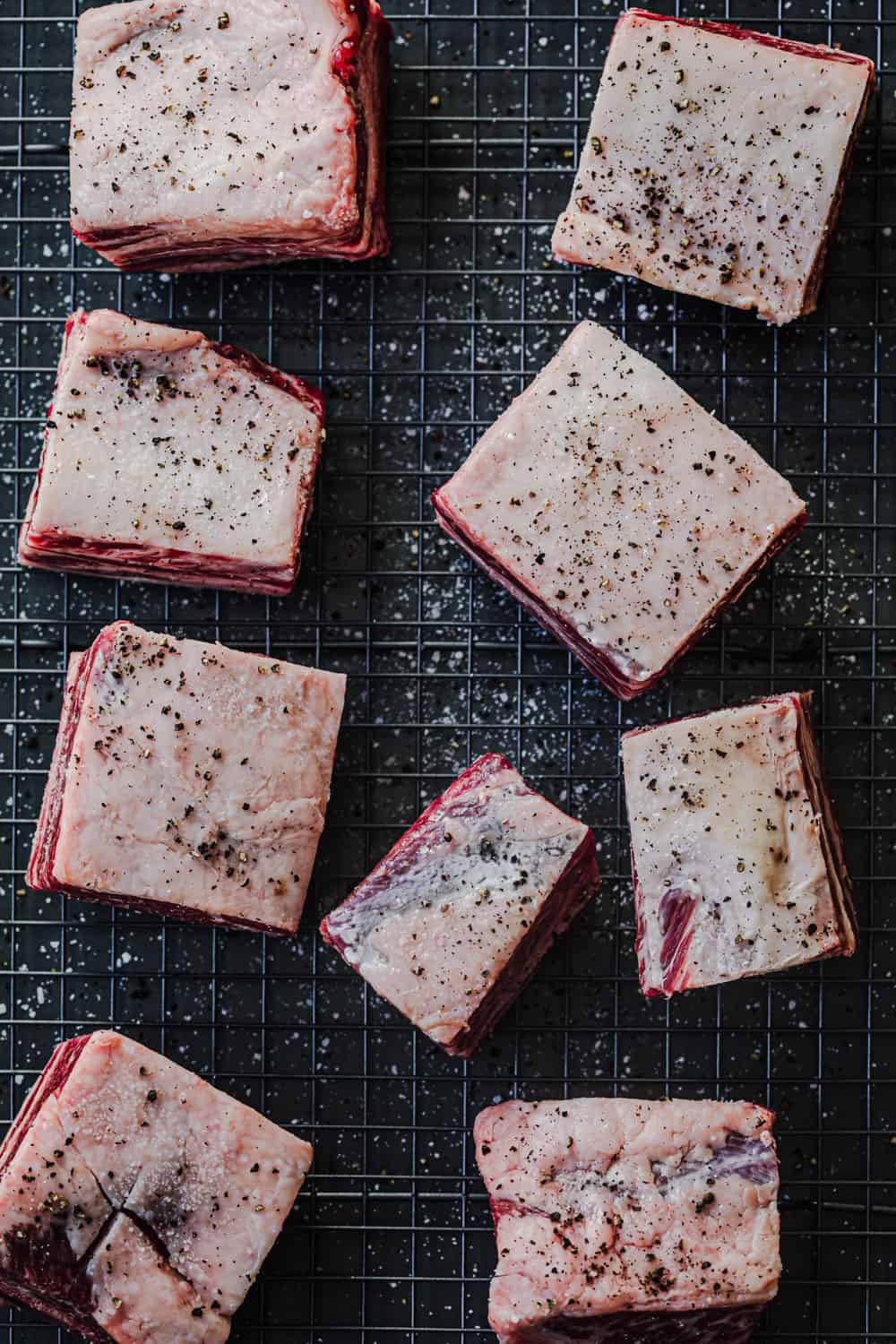ingredient shot: raw short ribs, seasoned with salt and pepper, on a wire rack on a baking tray.
