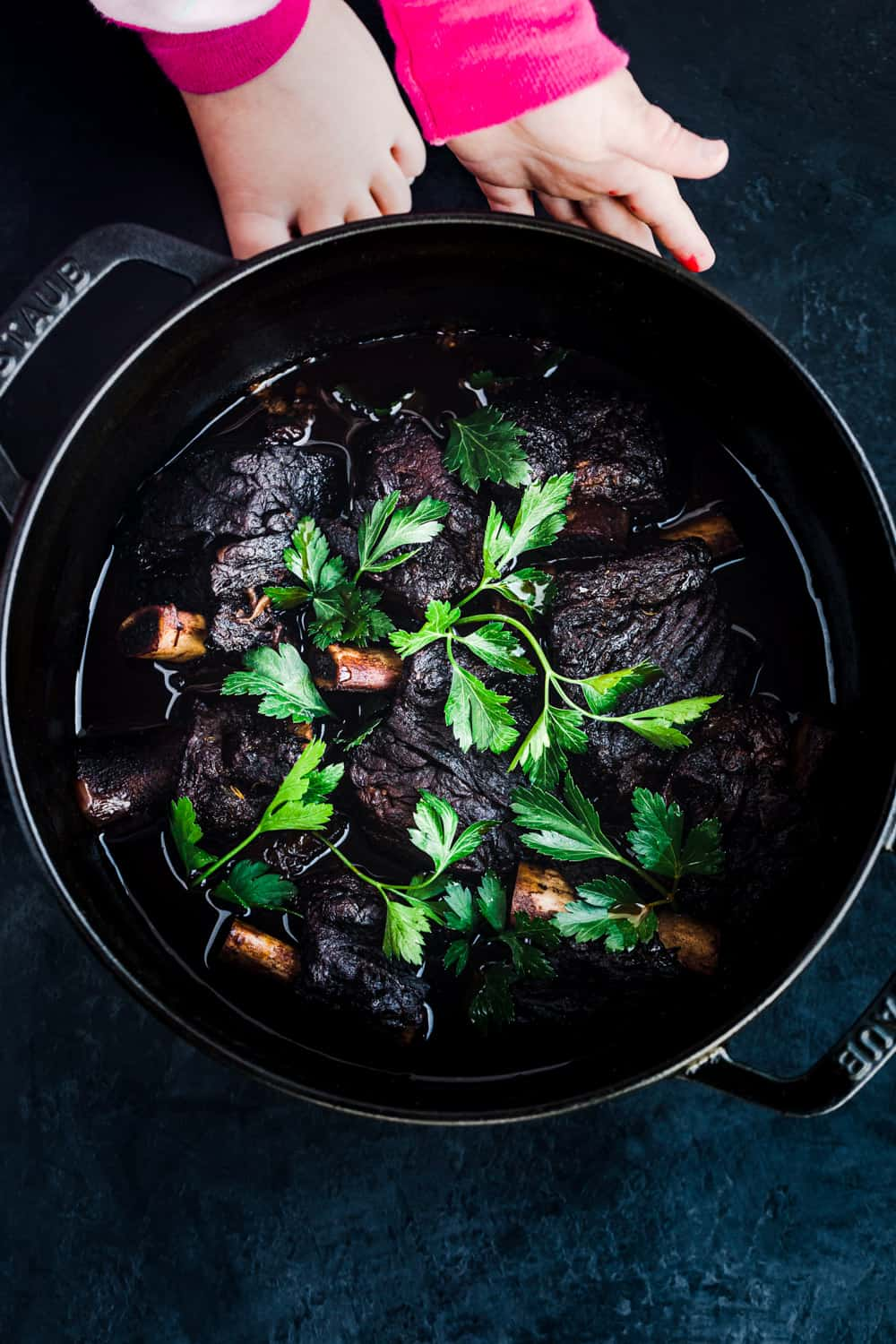 the best red wine braised short ribs, with a little hands cupping the cast iron dutch oven.