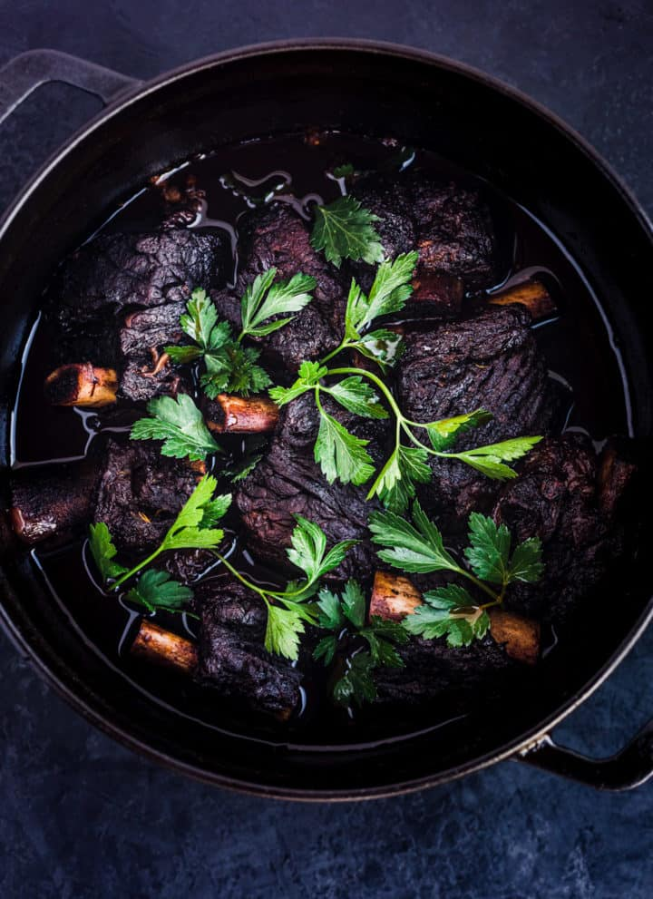 overhead shot of red wine braised short ribs, topped with parsley and ready to be served.