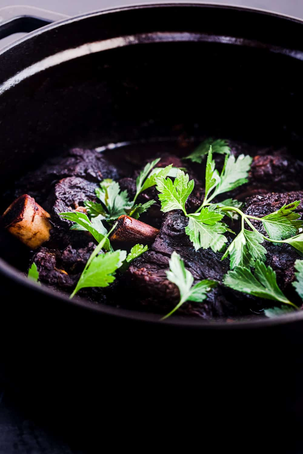 side angle shot of red wine braised short ribs, topped with parsley.