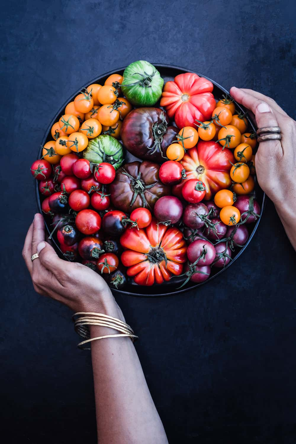 Daniela Gerson holding a black plate filled with rainbow tomatoes. They are all different varieties of seasonal heirloom tomatoes.