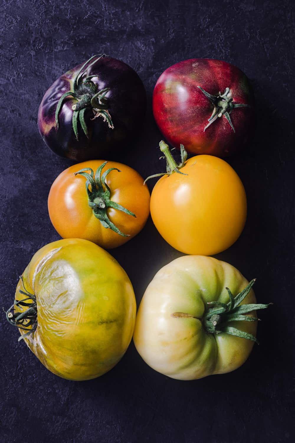 A tomato rainbow! 6 heirloom tomatoes in different colors: Deep purple, deep red, orange, yellow, yellow-green and green-white.