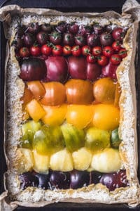 An heirloom tomato tart, overhead and pre-oven shot. The tomatoes are arranged on the dough like a rainbow, from red to purple.