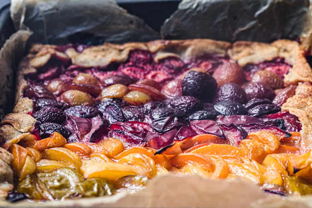Side angle horizontal shot of a stone fruit rainbow galette with fresh colorful summer fruit.