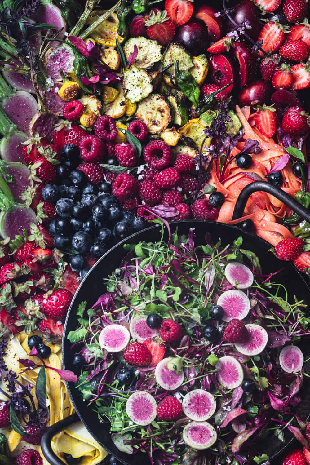 Summer fruit and veggie salad! There's berries, stone fruit, radishes, summer squash, greens and more arranged on a tray. Overhead shot.