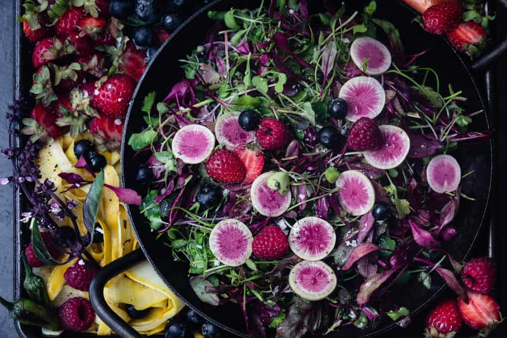 Summer squash and berry salad idea with greens arranged on a tray, overhead shot.