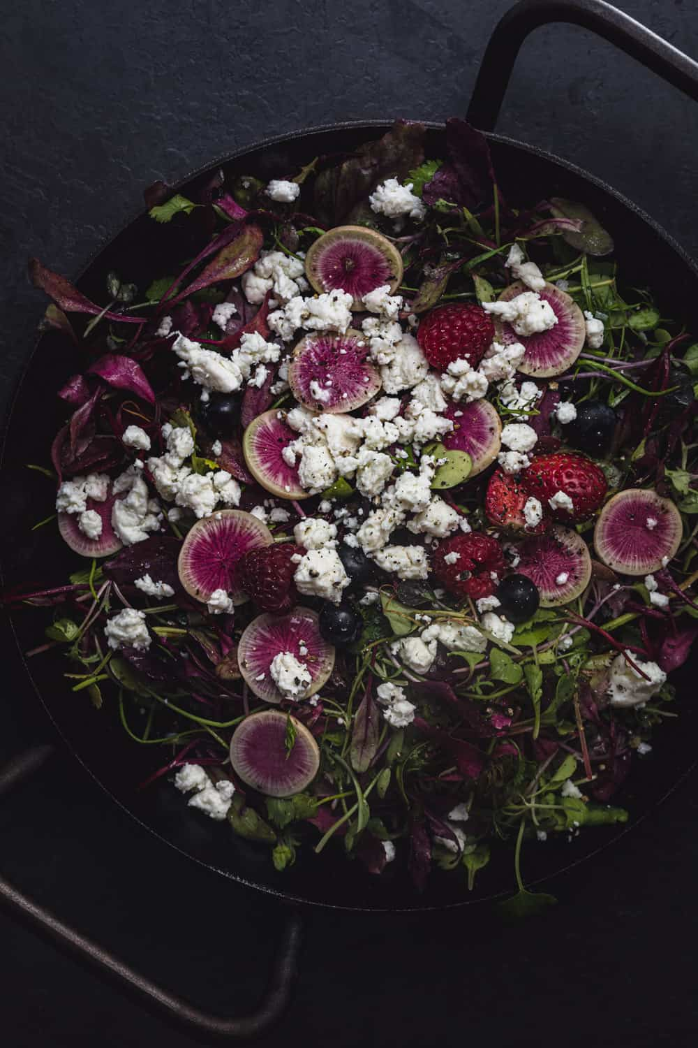 a summer green salad with berries, radishes, and cheese, overhead shot.