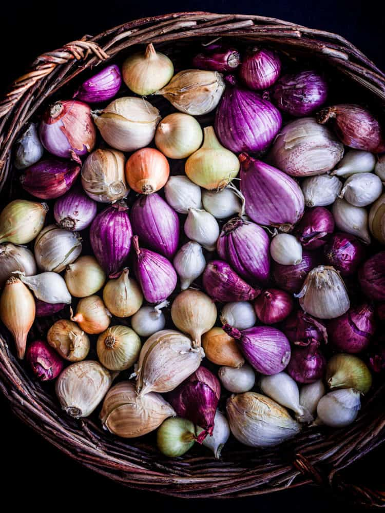 a basket filled with different varieties of colorful alliums - there's shallot, onions and garlic. Overhead shot on a black background.