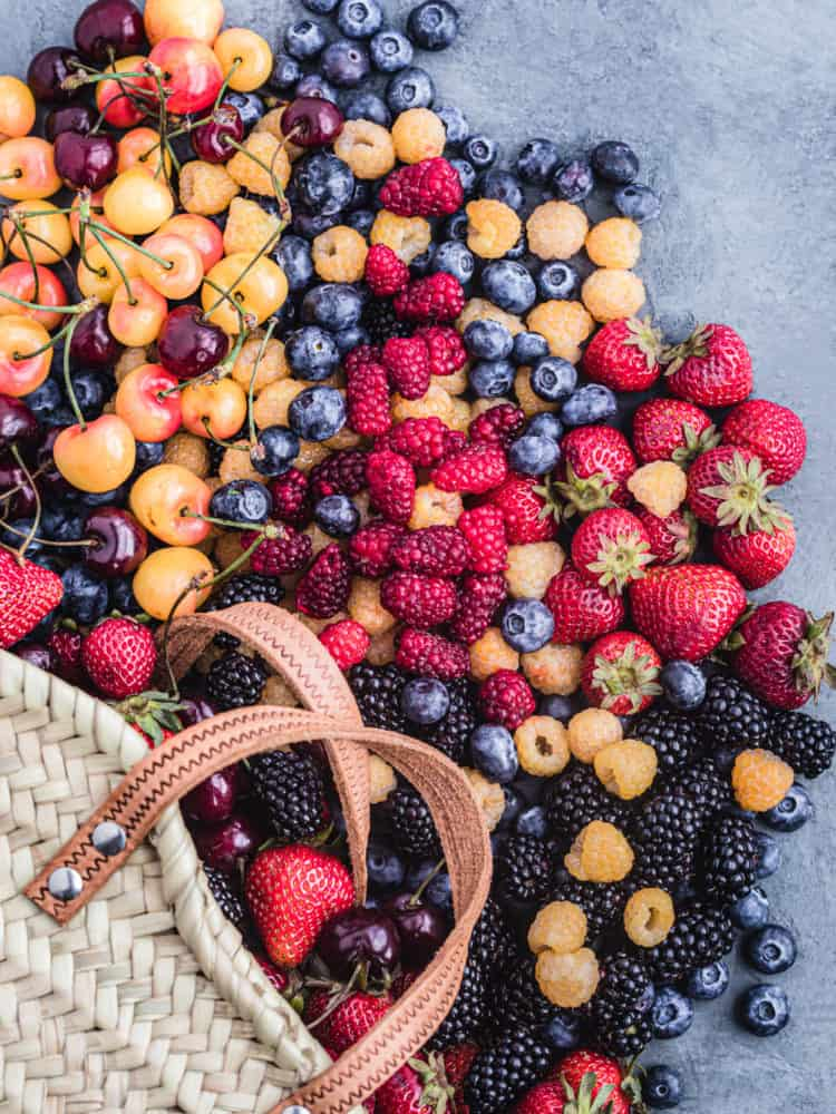 A bag overflowing with different kinds of colorful berries! There's strawberries, red and golden raspberries, tayberries, blueberries, golden and red cherries and blackberries; overhead shot on a grey background.