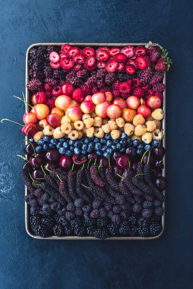 A sheet pan filled with a mixed berries in all the colors of the rainbow! There's red, orange, yellow, blue, purple, and all the hues in between! Overhead shot on a black background.