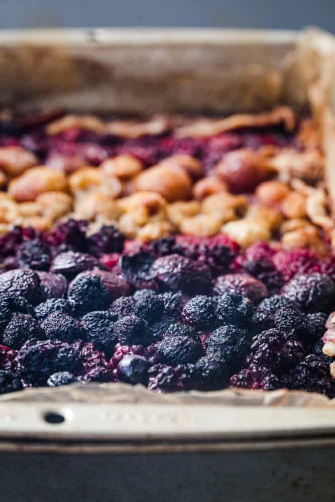 Side angle shot of mixed berry galette post oven, focus is on purple raspberries, mulberries and tayberries.