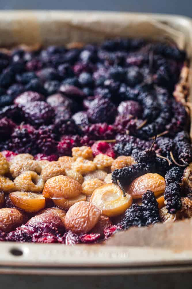 Side angle shot of mixed berry galette, focus is on golden cherries and strawberries post oven.
