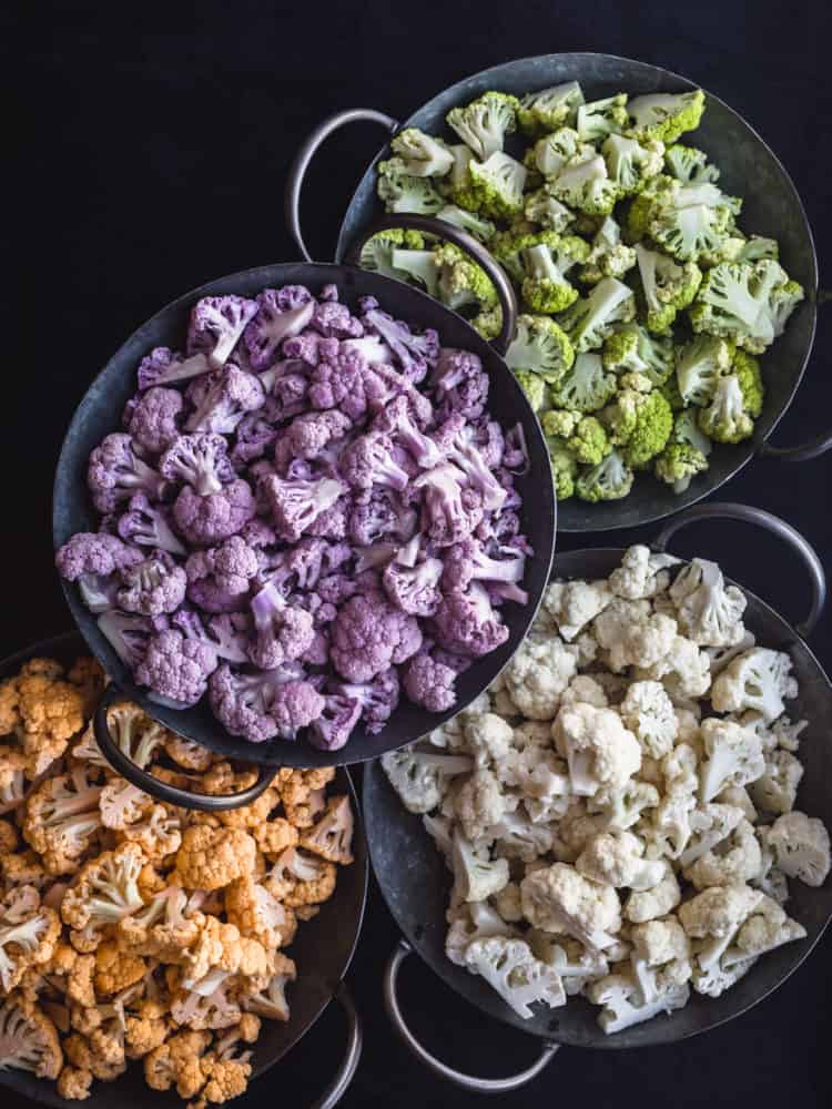 4 different colors of cauliwer cut up in a 4 bowls! There's orange, purple, white and green; overhead shot on a black background.