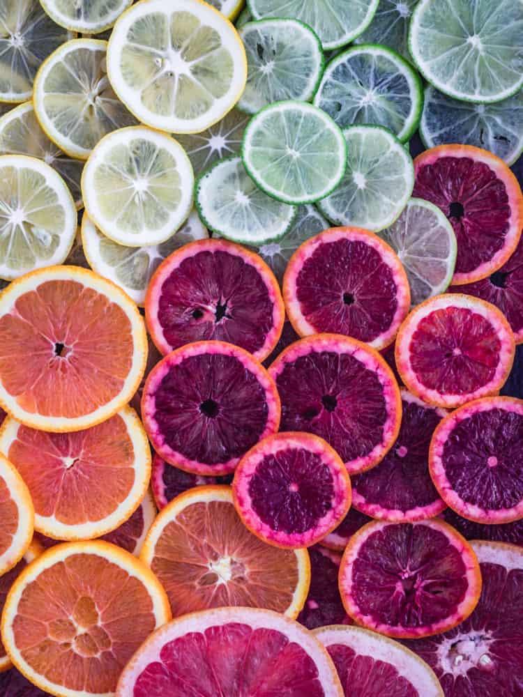 different varieties of colorful citrus slices including lemons, limes, oranges, blood oranges and grapefruits, overhead shot.
