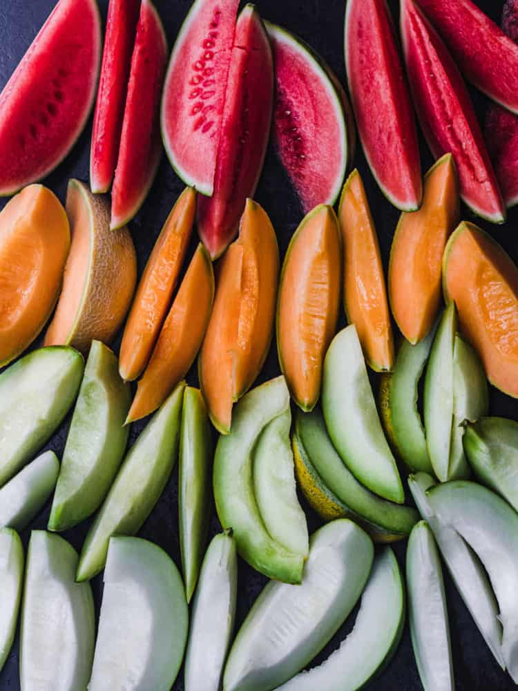 4 varieties of colorful melons! There's red-pink watermelon, orange catanloupe, and green and white melon; overhead shot on a black background.