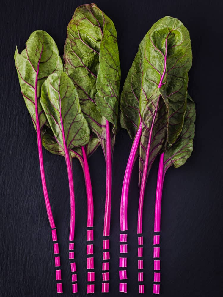 Swiss chard with hot pink stems cut into pieces and then arranged artistically; overhead shot on a black background.