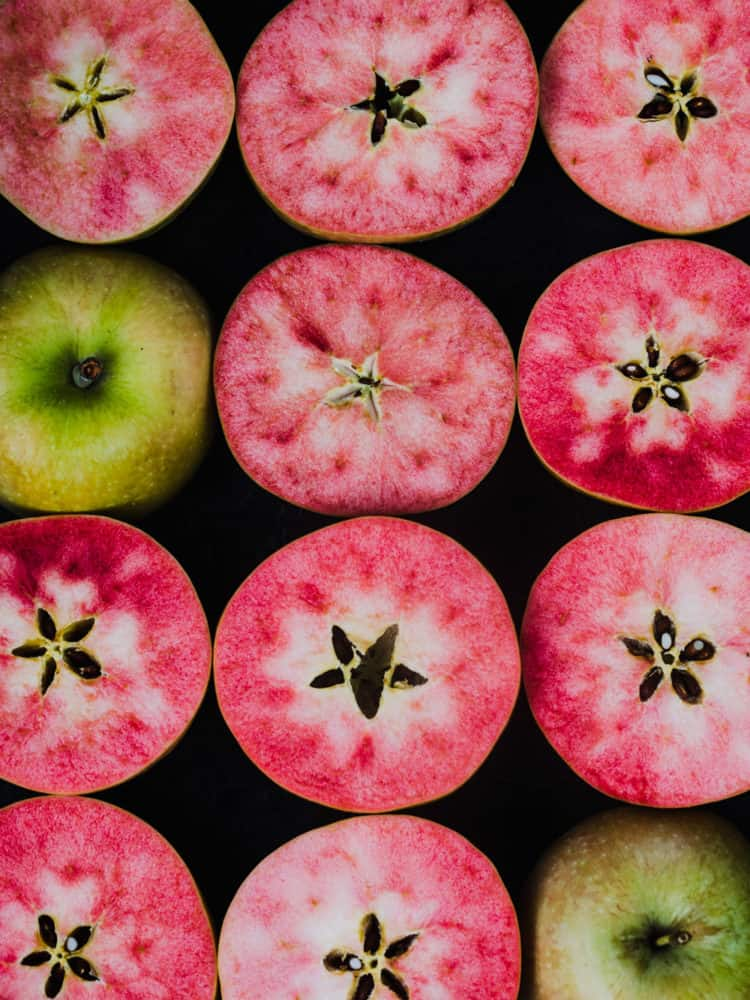 Pink hidden rose apples, cut in half to reveal their pink insides, overhead shot on a black background.