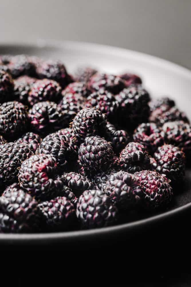 side angle shot of deep purple/black raspberries, up close so you can really see the raspberry texture.