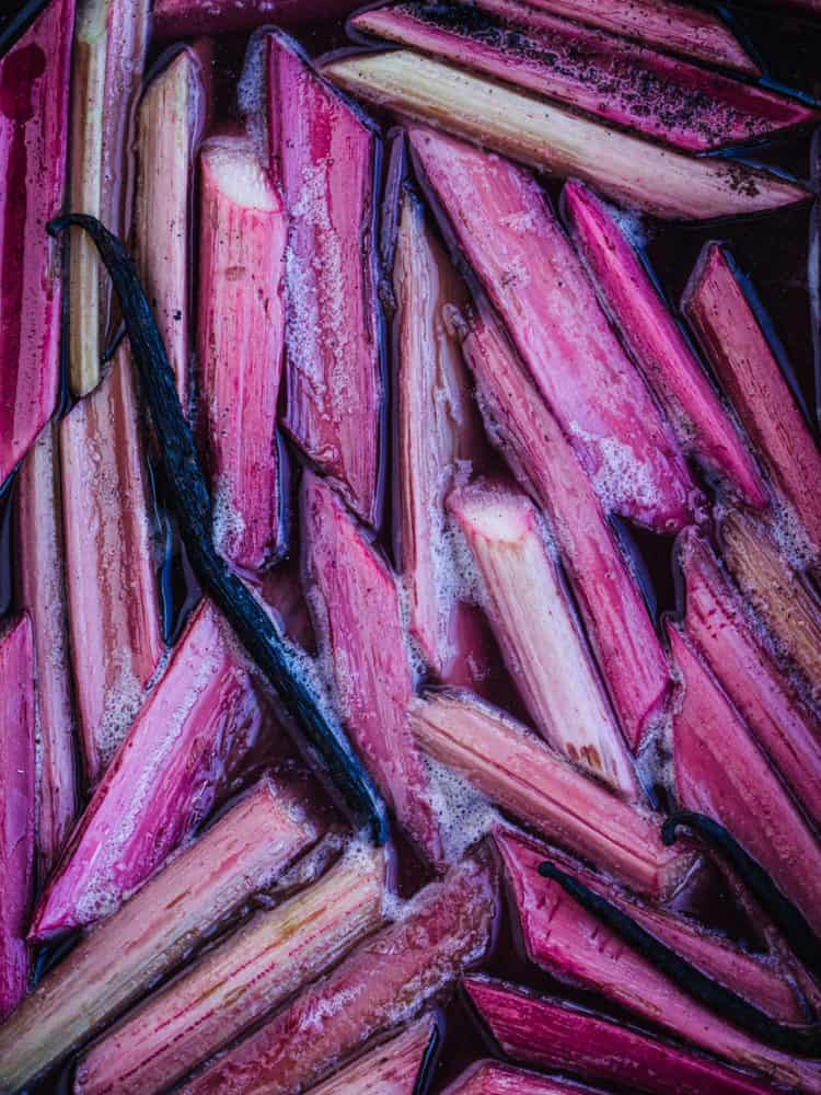Poached very pink rhubarb with vanilla, still in the pan, overhead shot.