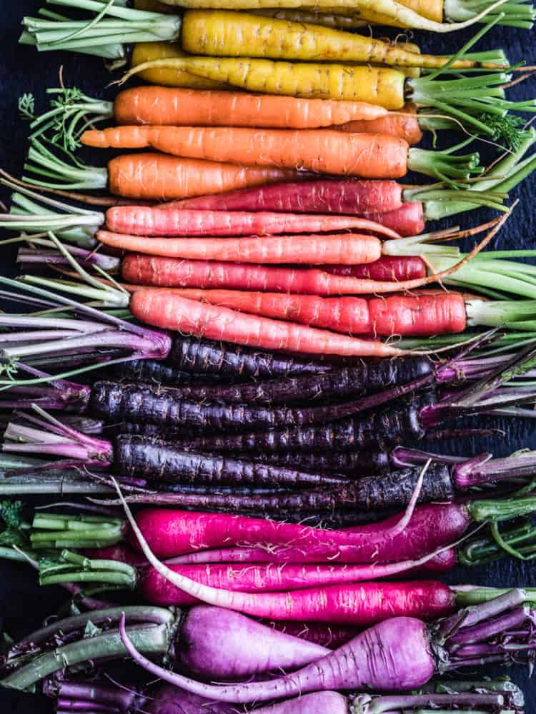 A root veggie rainbow! There's yellow, orange, coral and purple carrot and hot pink and purple radishes; overhead shot on a black background.