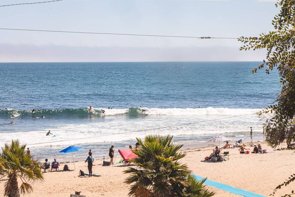 Surfers in Los Angeles! Surfers at Topanga beach! Can see some surfers sharing a waves and the sandy beach.