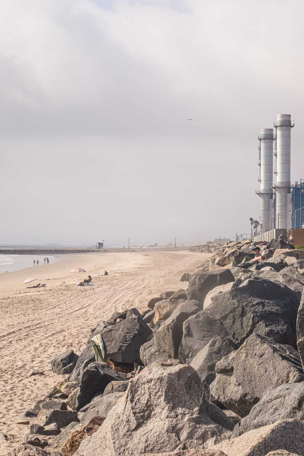 the smoke stacks at El Porto - Manhattan beach, you can see the ocean, waves and sand.