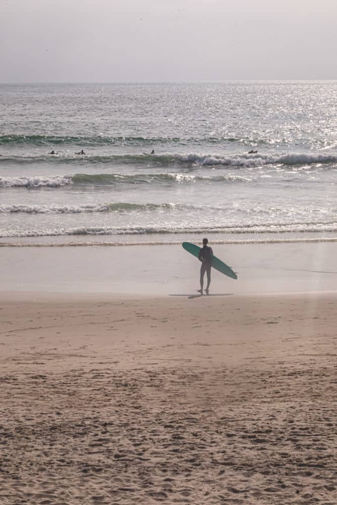 a surfer assessing the line up at El Porto, some surfers are in the ocean.