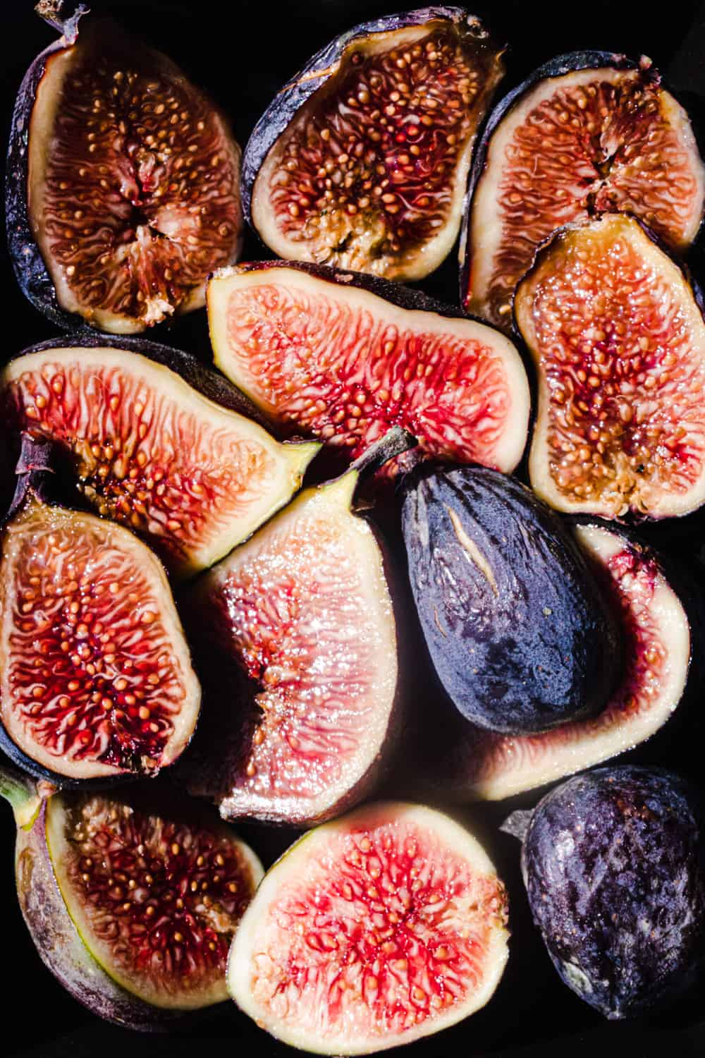 Perfectly ripe fresh figs cut in half, revealing theirs soft and jammy interior.