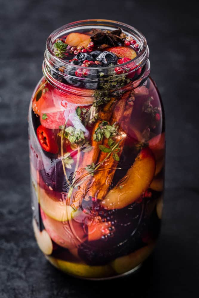 Mixed Pickled Fruit! Different fresh fruit in a jar with start anis, pink peppercorns, chili, thyme and pickling brine; side angle shot.