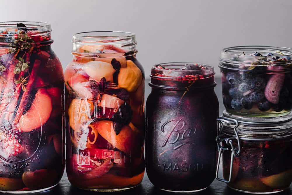5 different jars of pickled fruits! There's pickled peaches, pickled plums, pickled cherries, pickled blueberries, and pickled fruit, shot straight on.