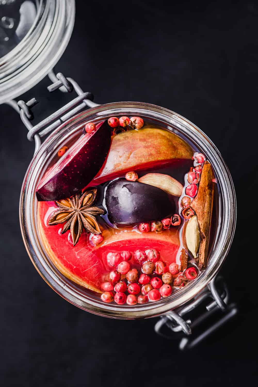 Pickled plums with star anise, cinnamon, pink peppercorns and pickling brine, overhead shot on a black background.