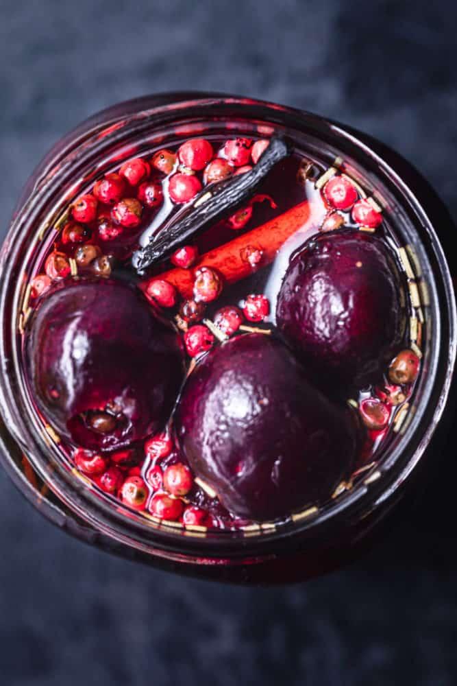 overhead shot of pickled cherries in jar. can see 3 cherries, vanilla, cinnamon, pink peppercorns, rosemary and pickling brine in the jar too.