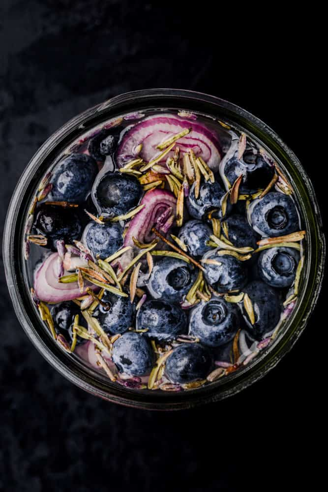 Pickled blueberries! Blueberries pickled with shallots, lavender, thyme and pickling brine; overhead shot.
