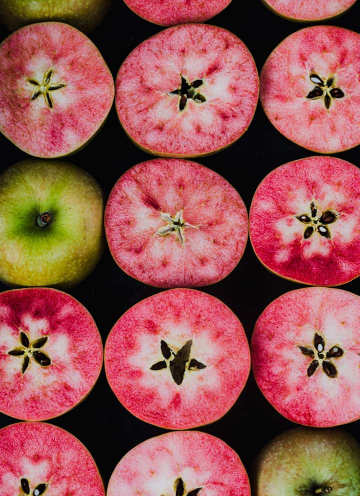 Pink apples, cut in half, revealing their pink flesh, overhead shot.