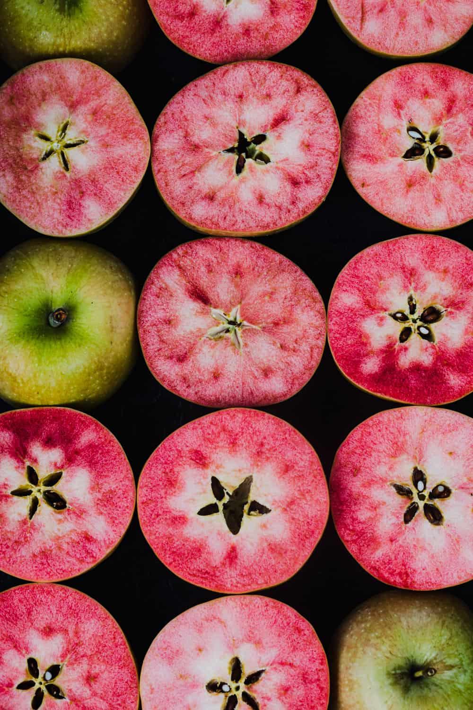 Pink apples, cut in half, revealing their pink flesh, overhead shot.