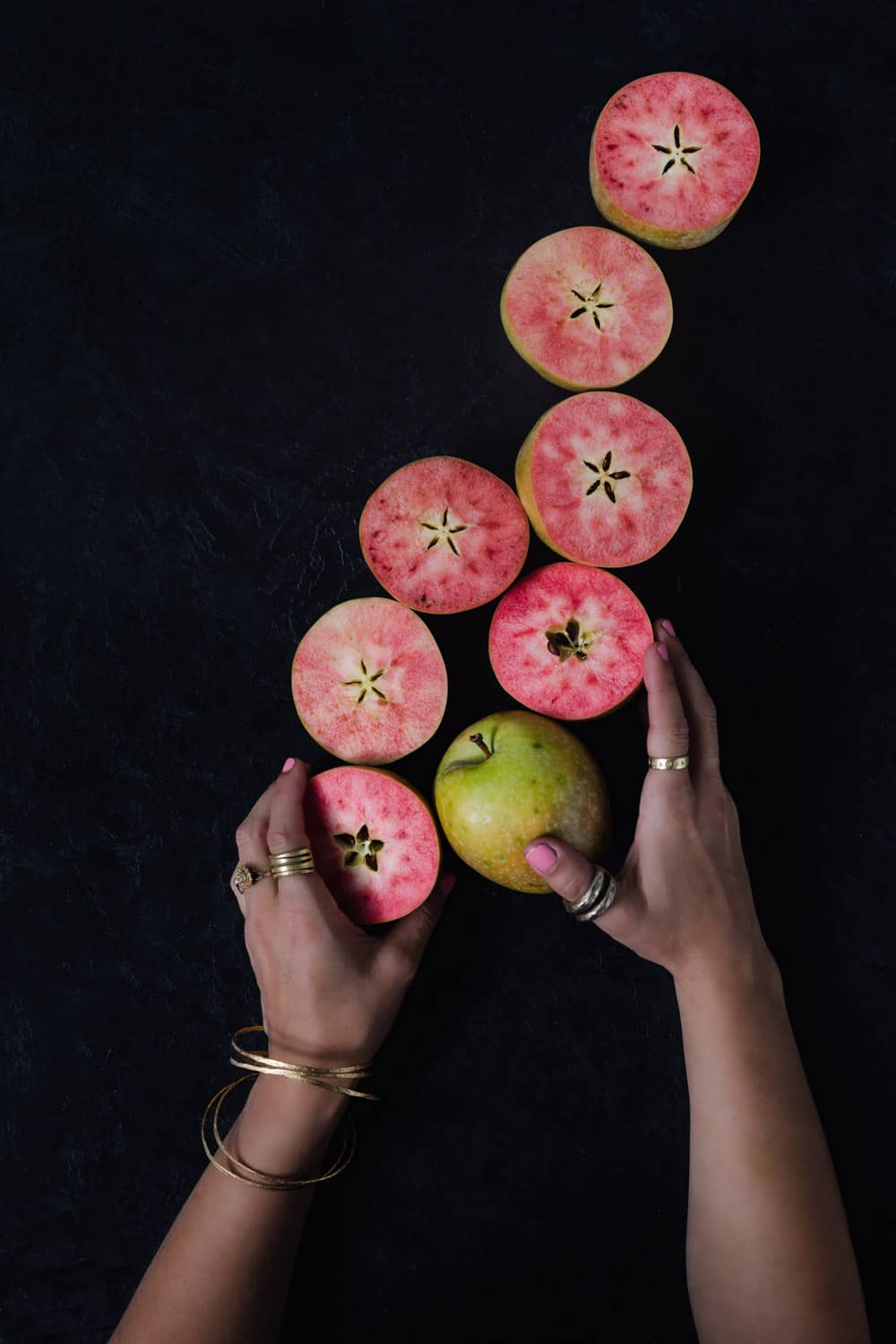 Daniela Gerson holding pink apples, overhead shot on a black background.