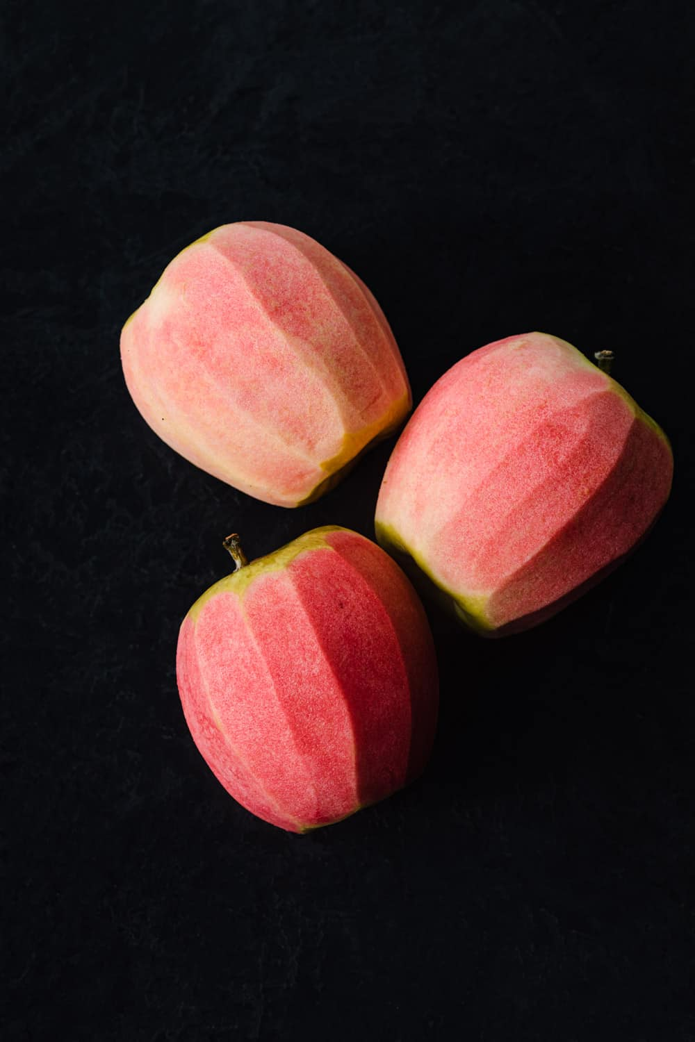 Hidden Rose apples, whole and peeled, revealing their pink flesh! Balck background, overhead shot.