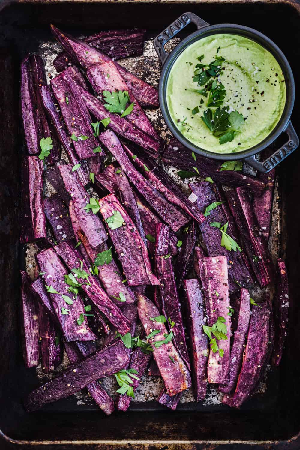 Purple sweet potatoes wedges in a baking dish with green tahini in a bowl, sprinkled with salt, pepper and parsley; overhead shot.