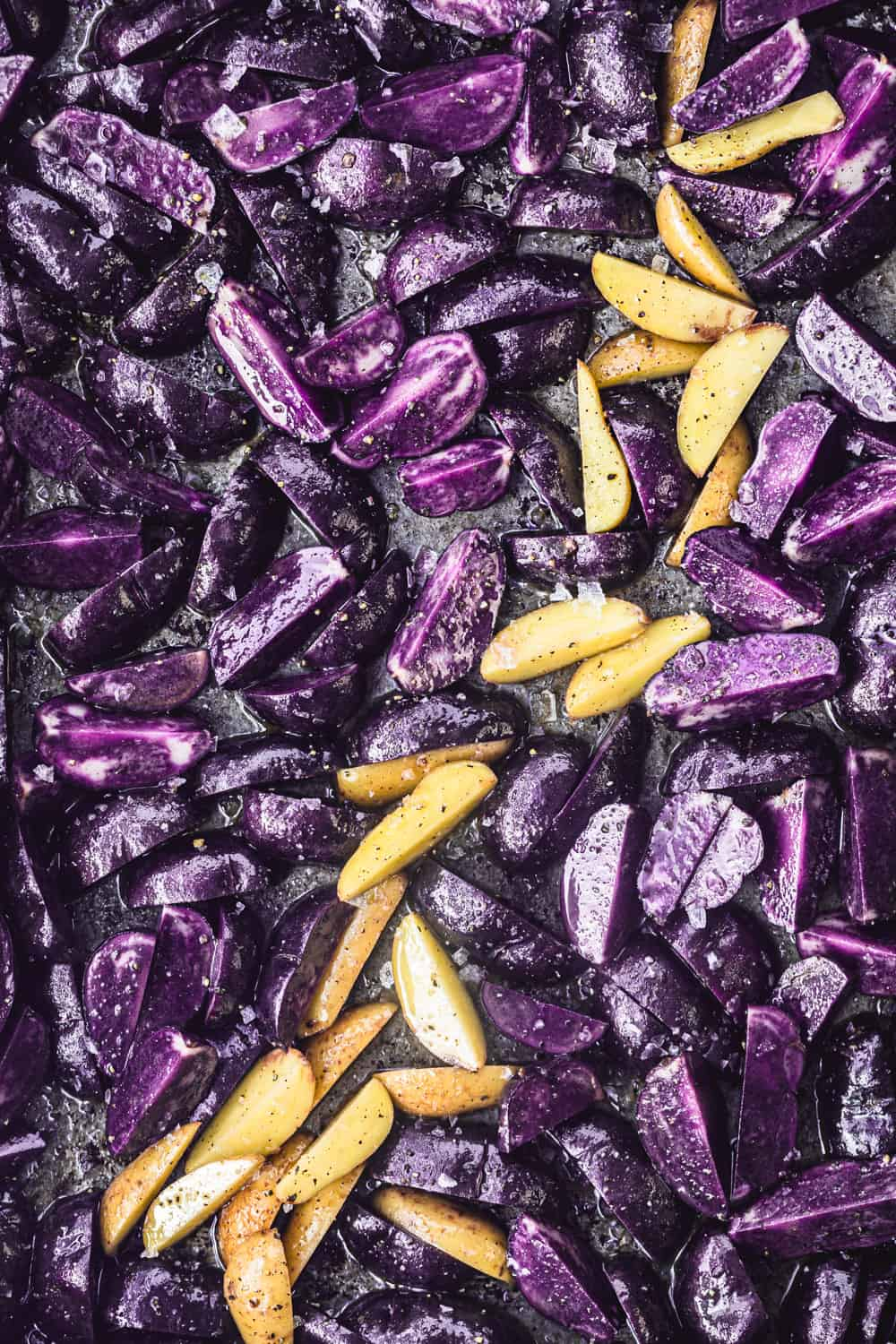 Little purple potatoes cut into wedges with a few white potatoes on the baking sheet as well; overhead shot.