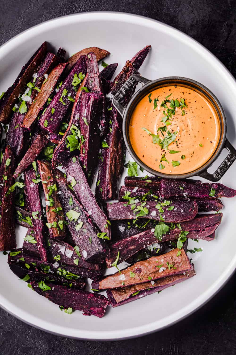 Purple sweet potato wedges in a white bowl served with chipotle aioli and sprinkled with salt, pepper, and parsley.